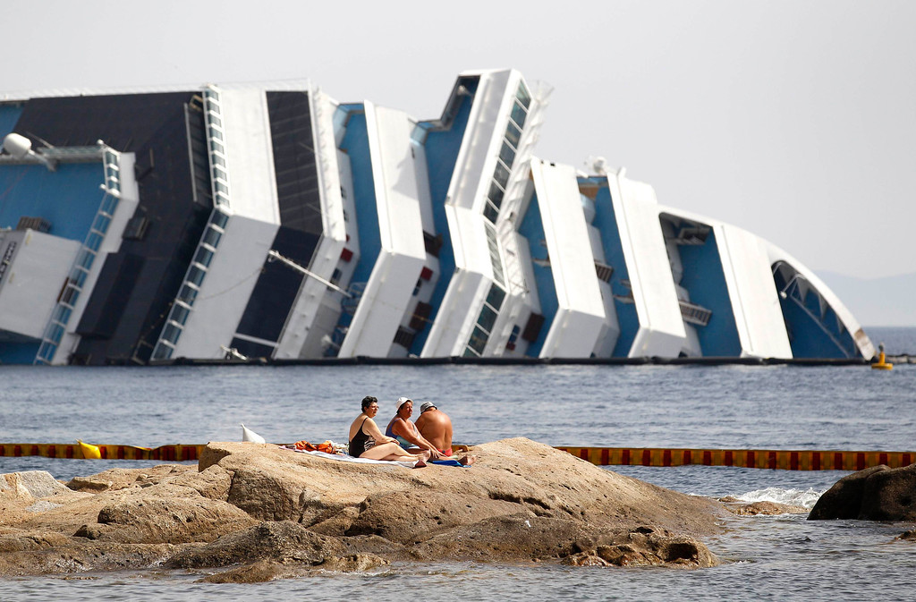 Description of . Vacationers bask in front of the wreckage of capsized cruise liner Costa Concordia near the harbour of Giglio Porto June 20, 2012.  The salvage operation to move the capsized Costa Concordia away from the island of Giglio, where it ran aground three months ago, will begin in June.        REUTERS/Max Rossi