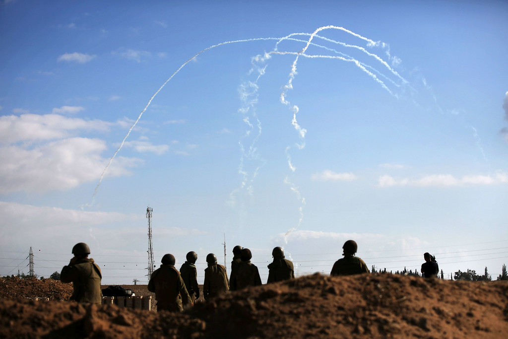 Description of . Israeli soldiers watch the smoke trails of 155mm shells fired at targets in the Gaza Strip, at an army deployment area near Israel's border with the Gaza Strip, on July 17, 2014. Israel and the Islamist Hamas movement have agreed on a ceasefire that will begin at 0300 GMT on Friday, an Israeli official told AFP. AFP PHOTO /MENAHEM KAHANA/AFP/Getty Images