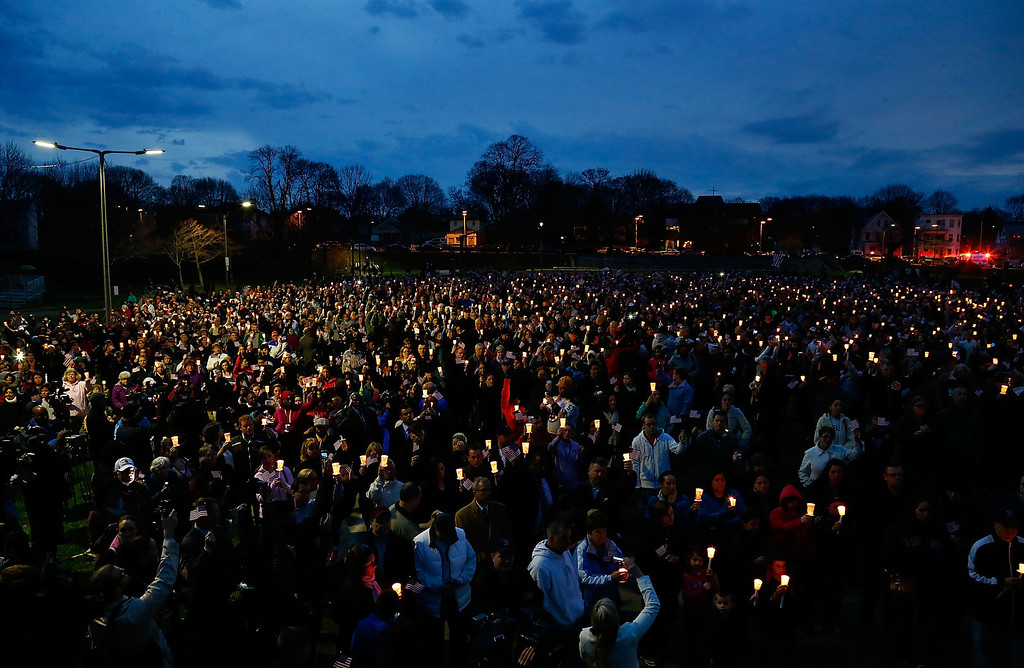 Description of . BOSTON, MA - APRIL 16: People gather with candles during a vigil for eight-year-old Martin Richard, from Dorchester, who was killed by an explosion near the finish line of the Boston Marathon on April 16, 2013 at Garvey Park in Boston, Massachusetts. The twin bombings resulted in the deaths of three people and hospitalized at least 128. The bombings at the 116-year-old Boston race resulted in heightened security across the nation with cancellations of many professional sporting events as authorities search for a motive to the violence. (Photo by Jared Wickerham/Getty Images)