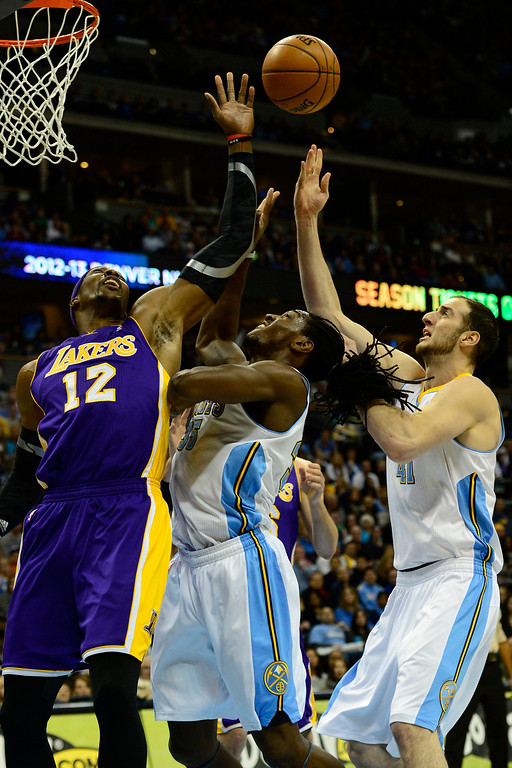 Description of . Los Angeles Lakers center Dwight Howard (12) contends for a rebound with Denver Nuggets small forward Kenneth Faried (35) and center Kosta Koufos (41) during the first half at the Pepsi Center on Wednesday, December 26, 2012. AAron Ontiveroz, The Denver Post