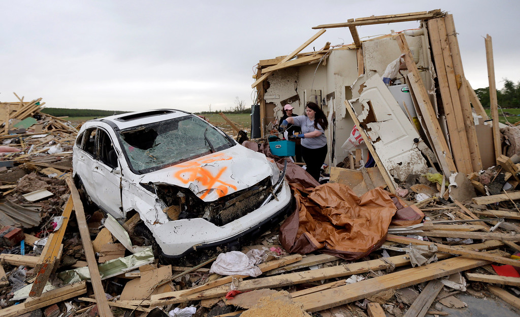 Description of . Haley Hracke, front, and Melissa Nichols, search for belongings at a friend's home that was destroyed by Sunday's tornado, Tuesday, April 29, 2014, in Vilonia, Ark.  (AP Photo/Eric Gay)