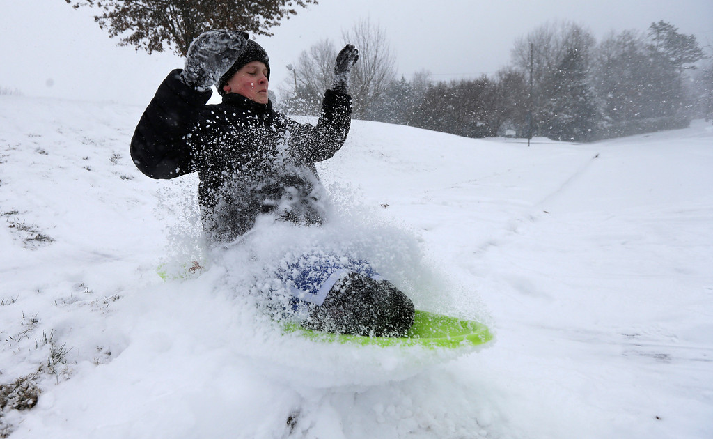 Description of . Stephen Clark, 12, hits a ramp made of snow near as he sleds near his home in Charlotte, N.C., Wednesday, Feb. 12, 2014, as a winter storm moves into the area. (AP Photo/Chuck Burton)