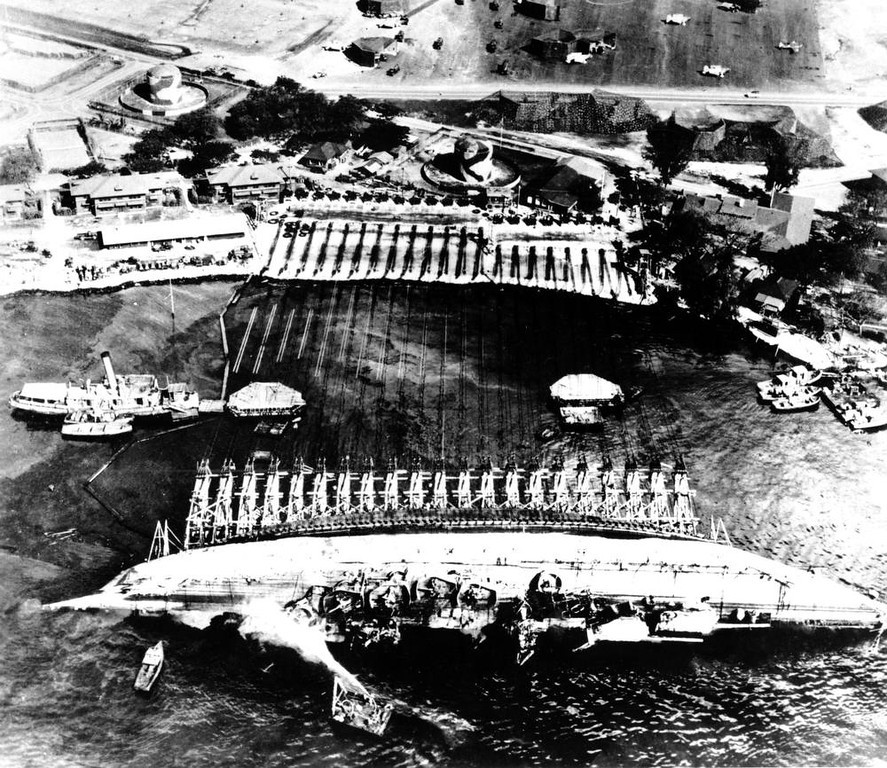 Description of . The stricken USS Oklahoma battleship lies half-righted as cables stretched over wooden A-frames to Ford Island at Pearl Harbor are used to right the ship in 1944.  The ship was hit by torpedoes and sunk in the Japanese attack on Pearl Harbor, Dec. 7, 1941 during World War II.  (AP Photo/U.S. Navy)