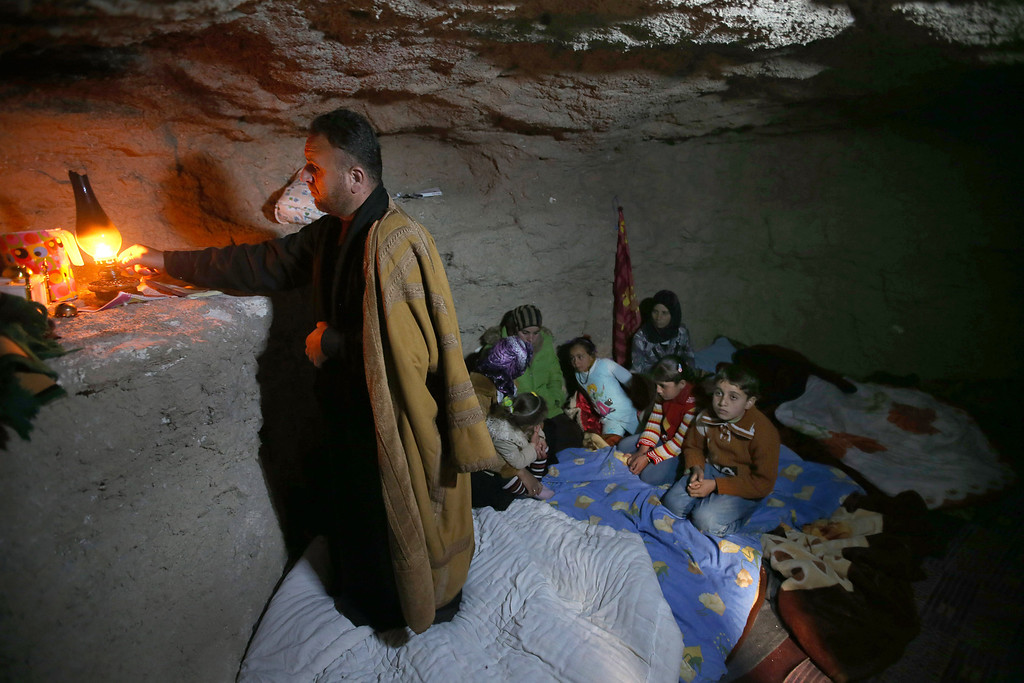 Description of . FILE - A defected Syrian policeman, Adnan al-Hamod, 33, lights a kerosene lamp at an underground cave used for shelter from Syrian government forces shelling and airstrikes, at Jirjanaz village, in Idlib province, Syria, Thursday Feb. 28, 2013. (AP Photo/Hussein Malla, File)
