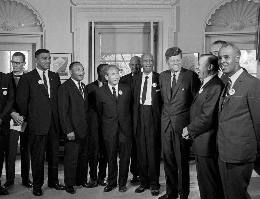 Description of . In this Aug. 28, 1963 file photo, President Kennedy stands with a group of leaders of the March on Washington at the White House in Washington. Immediately after the march, they discussed civil rights legislation that was finally inching through Congress. The leaders pressed Kennedy to strengthen the legislation; the president listed many obstacles. Some believe Kennedy preferred to wait until after the 1964 election to push the issue. Yet in his public speeches, he spoke more and more about justice for all. From second left are Whitney Young, National Urban League; Dr. Martin Luther King, Christian Leadership Conference; John Lewis, Student Non-violent Coordinating Committee, partially obscured; Rabbi Joachim Prinz, American Jewish Congress; Dr. Eugene P. Donnaly, National Council of Churches; A. Philip Randolph, AFL-CIO vice president; Kennedy; Walter Reuther, United Auto Workers; Vice President Lyndon B. Johnson, partially obscured, and Roy Wilkins, NAACP. (AP Photo)