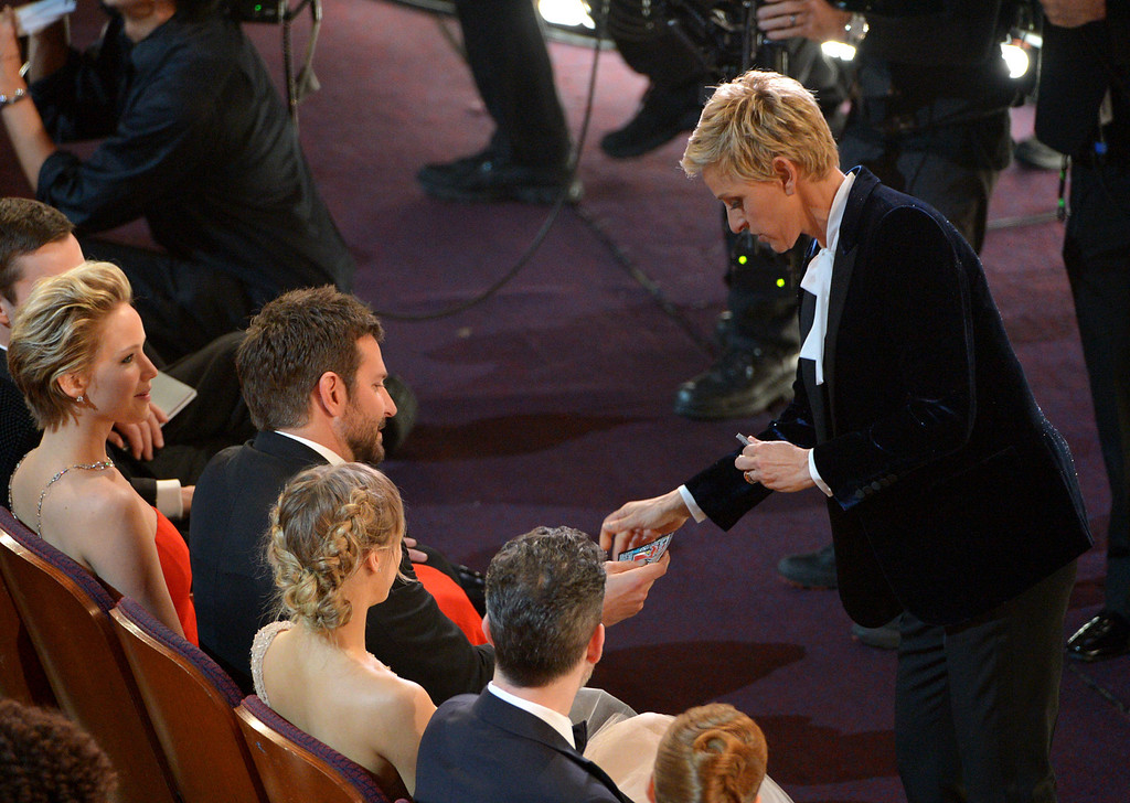 Description of . Ellen DeGeneres, right, gives Bradley Cooper a lottery ticket during the Oscars at the Dolby Theatre on Sunday, March 2, 2014, in Los Angeles.  (Photo by John Shearer/Invision/AP)
