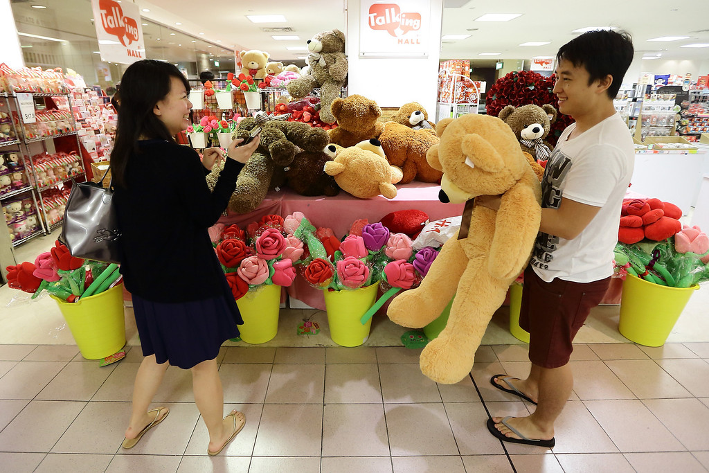 . A couple jokes around in a mall selling Valentine\'s day gift items at Orchard Road on February 14, 2013 in Singapore. Valentine\'s Day is a time to celebrate love, romance and friendship and is celebrated worldwide annually in different ways on February 14. (Photo by Suhaimi Abdullah/Getty Images)