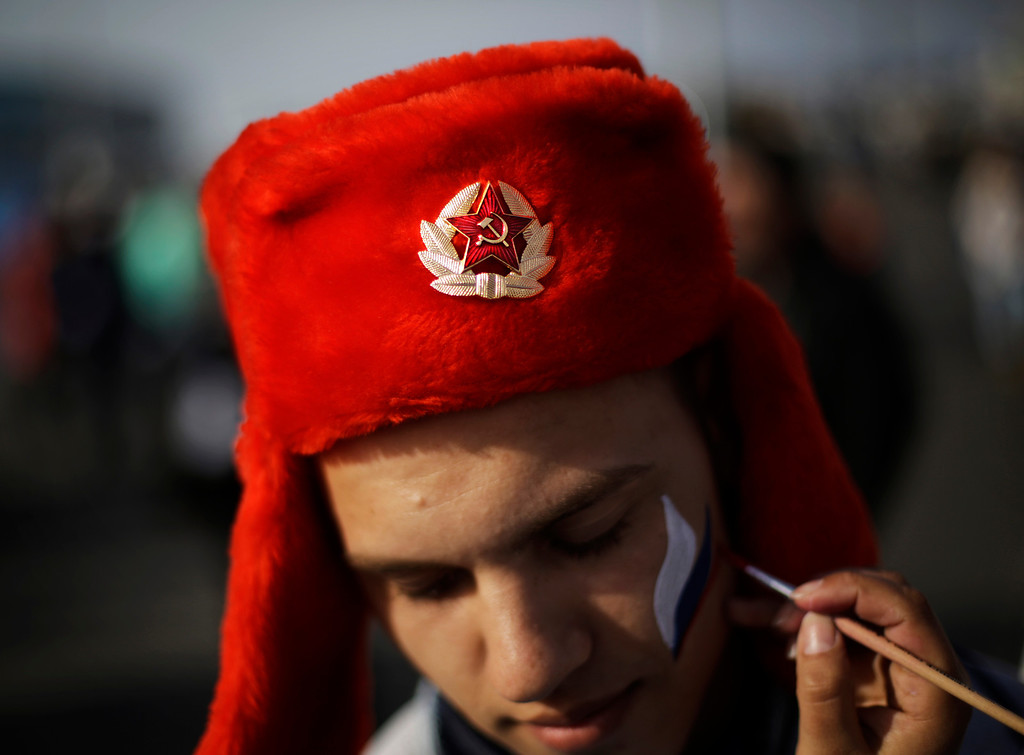 Description of . An emblem with the Soviet hammer and sickle decorates the hat of Serdar Yuldashev as he has his face painted in the colors of the Russian flag at the Olympic Park at the 2014 Winter Olympics, Thursday, Feb. 20, 2014, in Sochi, Russia. (AP Photo/David Goldman)
