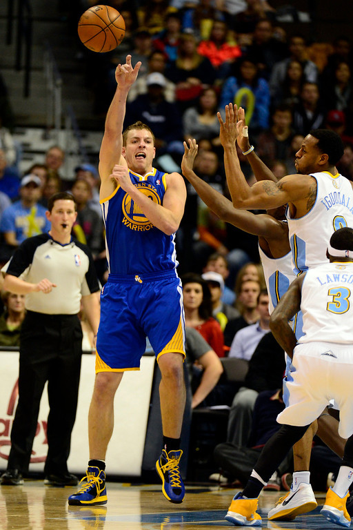 Description of . Golden State Warriors power forward David Lee (10) is forced to pass by Denver Nuggets shooting guard Andre Iguodala (9)  during the first half at the Pepsi Center on Sunday, January 13, 2013. AAron Ontiveroz, The Denver Post