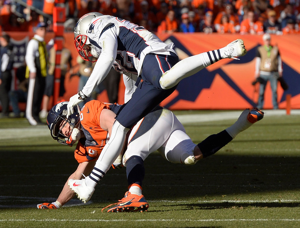 Description of . Denver Broncos wide receiver Wes Welker (83) is tackled by New England Patriots free safety Devin McCourty (32) after making a catch in the second quarter. The Denver Broncos vs. The New England Patriots in an AFC Championship game  at Sports Authority Field at Mile High in Denver on January 19, 2014. (Photo by Joe Amon/The Denver Post)