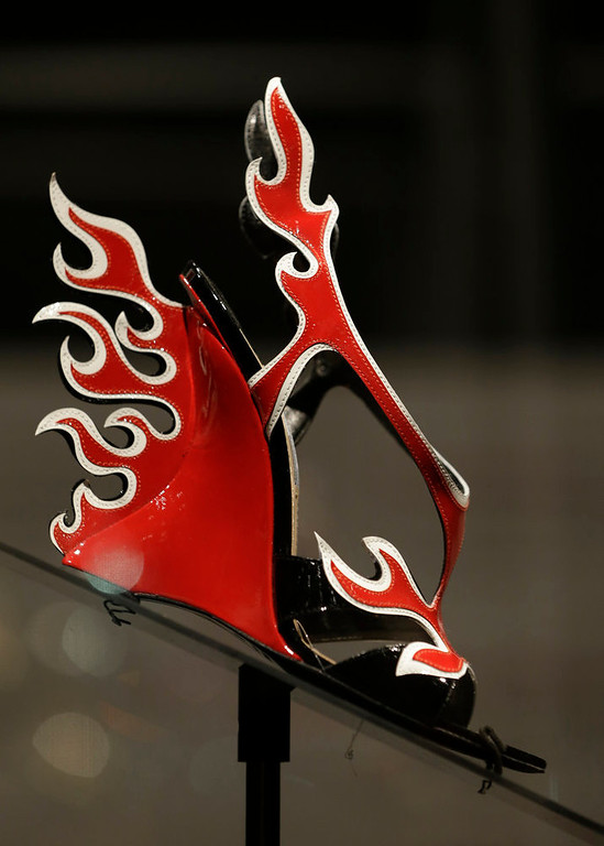 Description of . A red and white patent leather flame Prada sandal displayed at the