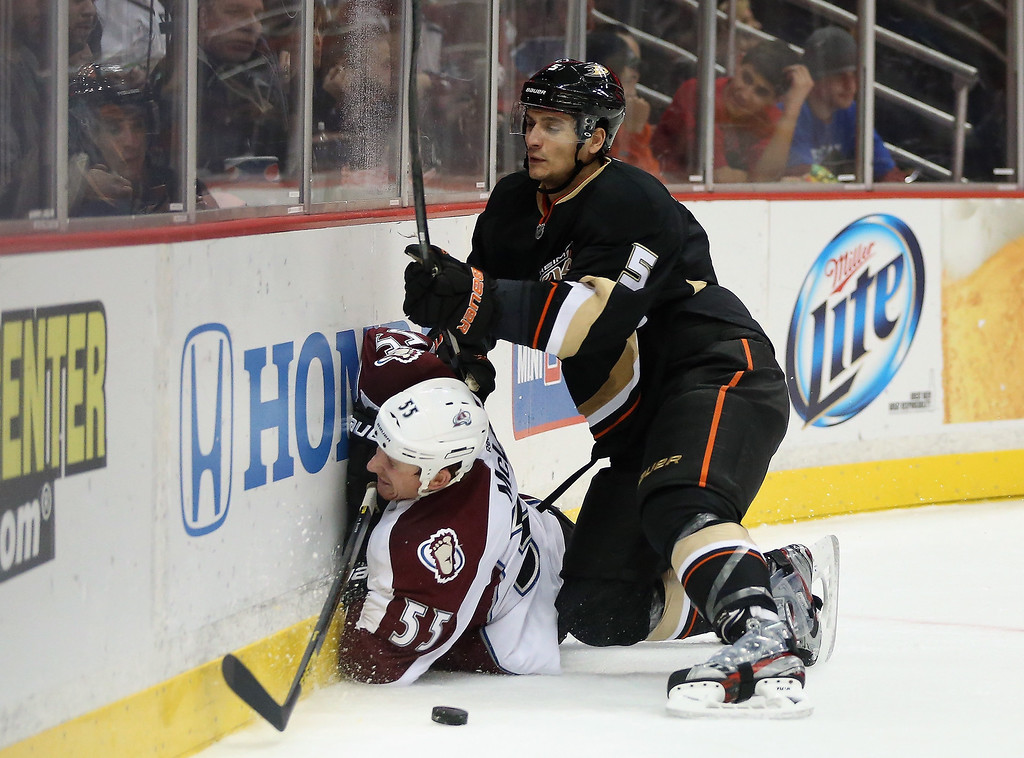 Description of . Cody McLeod #55 of the Colorado Avalanche is checked into the boards by Luca Sbisa #5 of the Anaheim Ducks in the second period at Honda Center on February 24, 2013 in Anaheim, California.  (Photo by Jeff Gross/Getty Images)