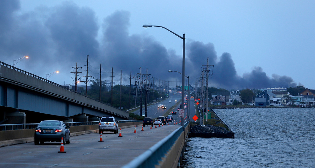 Description of . Commuters drive on a bridge connecting the barrier island of Seaside Heights, N.J., with the mainland as cloud of smoke rises from a massive fire at the Seaside Park boardwalk, Thursday, Sept. 12, 2013, in Seaside Park, N.J. The fire, which apparently started in an ice cream shop and spread several blocks, hit the recently repaired boardwalk, which was damaged last year by Superstorm Sandy. There were no other early reports of any injuries. (AP Photo/Julio Cortez)