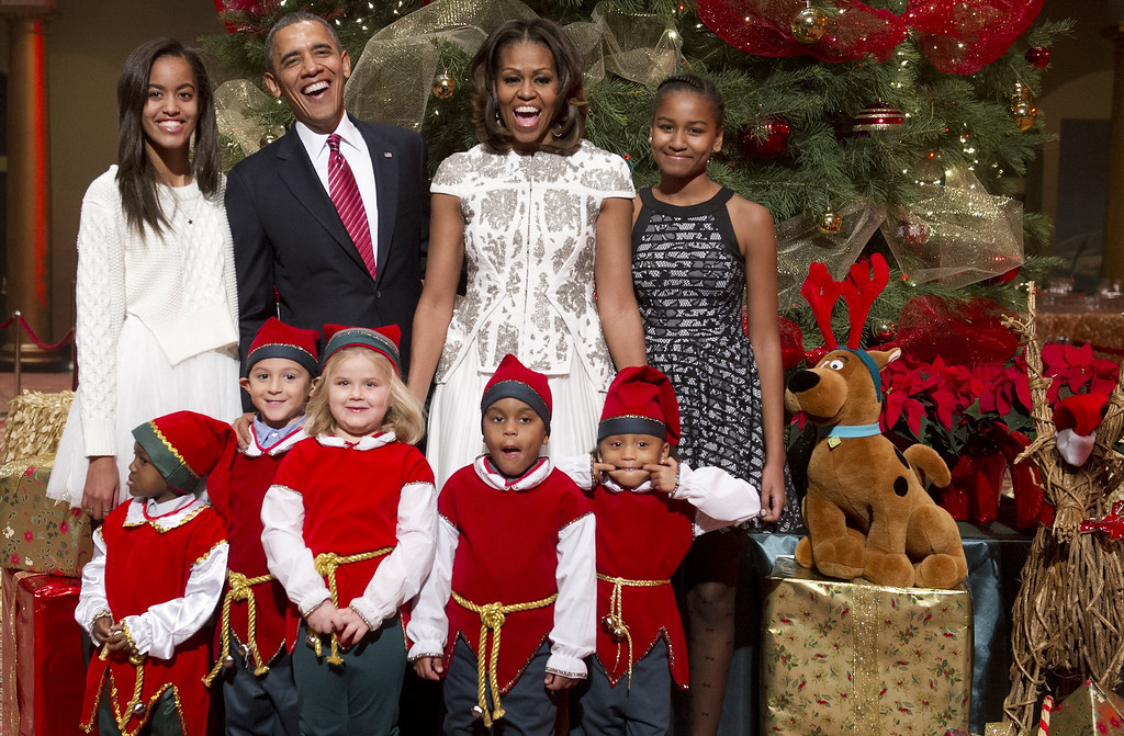 Description of . US President Barack Obama, First Lady Michelle Obama and their daughters, Sasha (R) and Malia (L), pose for photographs alongside children dressed as elves, who are or were patients at Children's National Medical Center after they presented donated gifts to the Obamas to give to children at the hospital, as they attend a taping of TNT's Christmas in Washington at the National Building Museum in Washington on December 15, 2013. The annual event, hosted by actor Hugh Jackman, features performances by the Backstreet Boys, Anna Kendrick, Sheryl Crow, Janelle Monae and Pat Monahan, and airs on the TNT television network on December 20.   SAUL LOEB/AFP/Getty Images