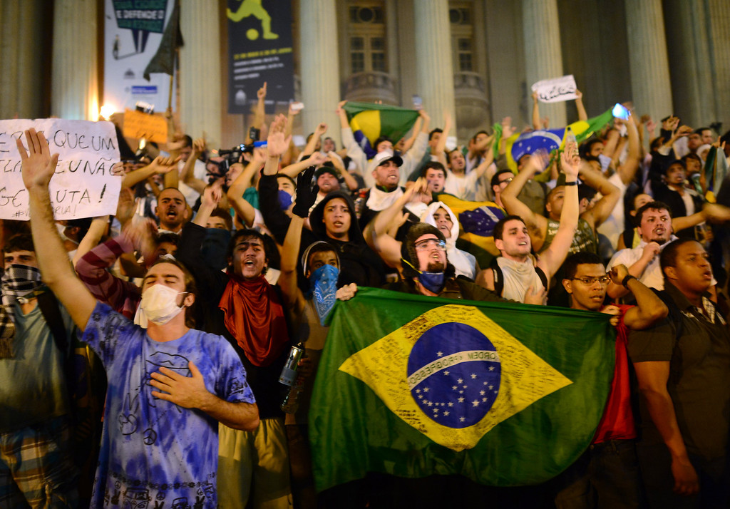 Description of . Demonstrators shout slogans outside the Municipal theatre in downtown Rio de Janeiro on June 17, 2013, during a protest against higher public transportation fares and the use of public funds to finance international football tournaments. Protesters in several major cities are up in arms over hikes in mass transit prices -- from $1.5 to $1.6 -- as well as over the $15 billion earmarked for the two sports events amid calls for more health and education funding.   CHRISTOPHE SIMON/AFP/Getty Images