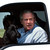 President Bush shows his dog Barney to the photographers before he drives back to his ranch house after a press briefing with his economic advisors on the ranch in Crawford, Texas Wednesday, Aug. 13, 2003.  Behind him, partially visible, is Labor Secretary Elaine Chao. (AP Photo/Gerald Herbert)