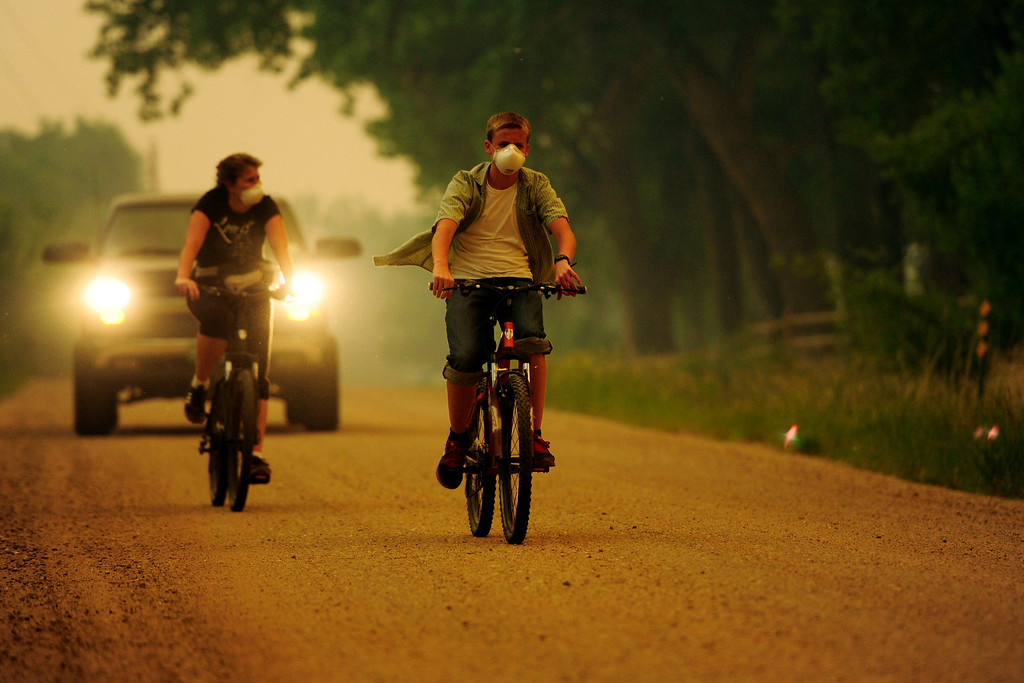 Description of . Caleb Armstrong and his mother, Cheryl, ride their bicycles near their home on County Road 56 as the High Park fire burns west of Fort Collins and Loveland on Sunday, June 10, 2012. The rapidly growing High Park fire is now burning an estimated 2,000 to 3,000 acres west of Fort Collins and Loveland, according to the Larimer County Sheriff's Office. AAron Ontiveroz, The Denver Post