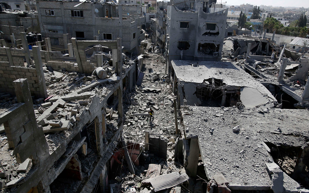 Description of . A Palestinian walks though a heavily bombed area in Beit Hanoun, Gaza Strip, Friday, Aug. 1, 2014. A three-day Gaza cease-fire that began Friday quickly unraveled, with Israel and Hamas accusing each other of violating the truce. (AP Photo/Hatem Moussa)