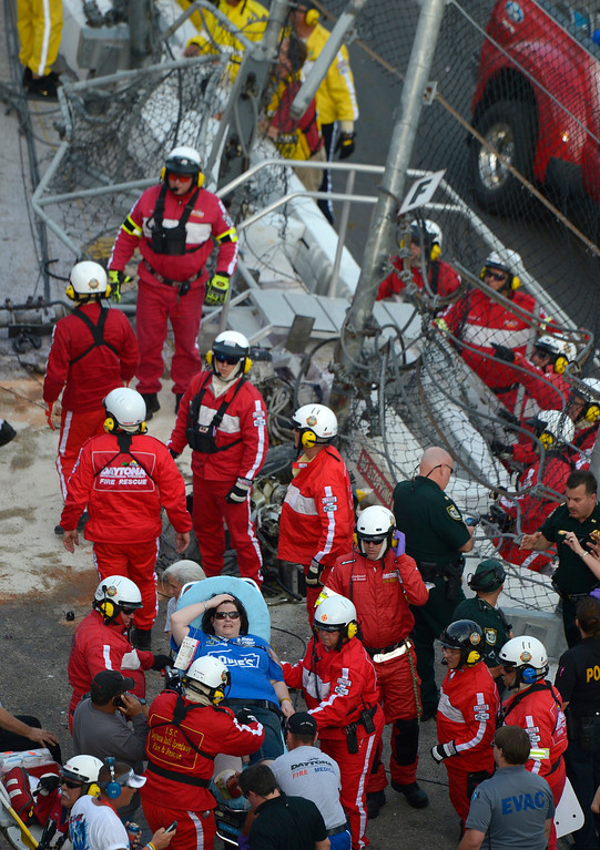 Description of . Emergency officials transport a fan who was hit by debris after Kyle Larson's car slammed into the wall and safety fence along the front grandstands on the final lap of the NASCAR Nationwide Series auto race at Daytona International Speedway in Daytona Beach, Fla., Saturday, Feb. 23, 2013.(AP Photo/Phelan M. Ebenhack)