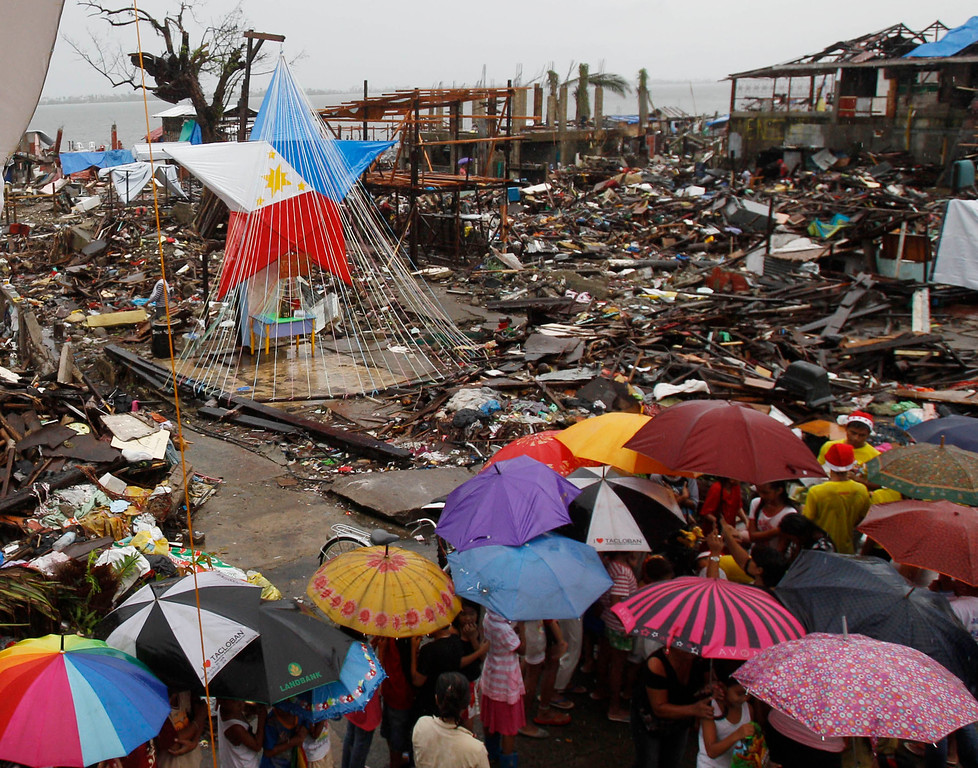 Description of . Children line up to receive a Christmas gift from volunteers near a giant lantern with the colors of the Philippine flag, in Tacloban, Philippines, Wednesday, Dec. 25, 2013. Mostly, Christmas is a celebration amid deprivation, in tents, makeshift homes and damaged churches in the city devastated by the Nov. 8 typhoon Haiyan. (AP Photo/Achmad Ibrahim)