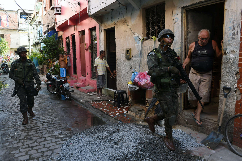 Description of . Brazilian soldiers patrol Vila Pinheiro --part of the Mare shantytown complex near the Galeao (Antonio Carlos Jobim) international airport-- in the north suburb of Rio de Janeiro on April 5, 2014. Thousands of soldiers --including some 2,000 paratroopers, 450 sailors and 200 military police-- in armored vehicles, trucks and on foot entered one of Rio de Janeiro's most notorious slums to provide security less than three months before the World Cup and until July 30. CHRISTOPHE SIMON/AFP/Getty Images