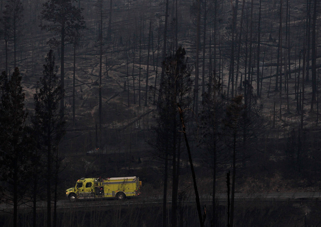 Description of . A fire truck drives past trees burned during the Las Conchas fire in Los Alamos, N.M., Thursday, June 30, 2011.   (AP Photo/Jae C. Hong)