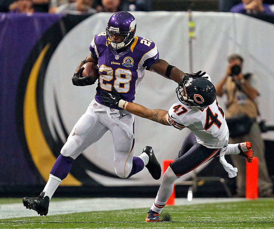 . Minnesota Vikings running back Adrian Peterson (28) pushes off of Chicago Bears safety Chris Conte (47) for a 14-yard gain during the first half of their NFL football game in Minneapolis, December 9, 2012. REUTERS/Eric Miller