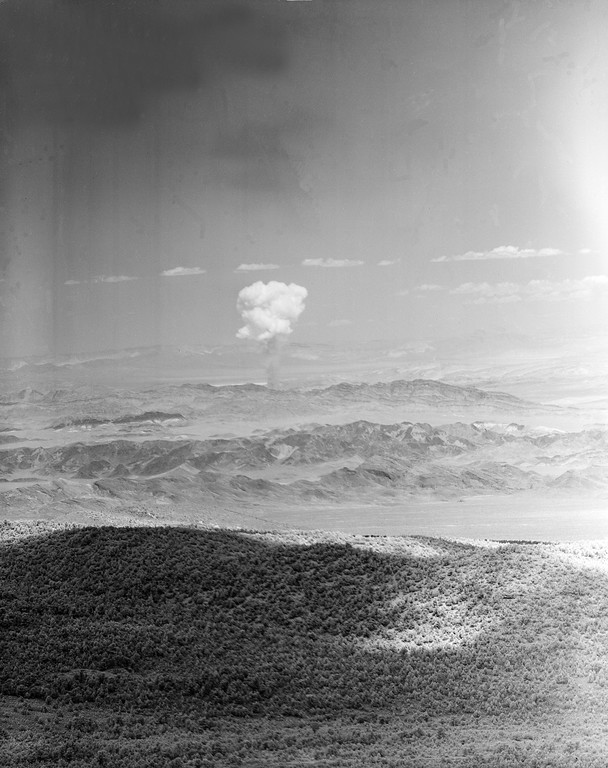 Description of . A column of debris and smoke rises from the atomic testing grounds northwest of Las Vegas, Nev., July 14, 1962.  The firing of the atomic device was the first large scale nuclear explosion in the atmosphere at the testing grounds since tests were suspended in 1958.  (AP Photo)