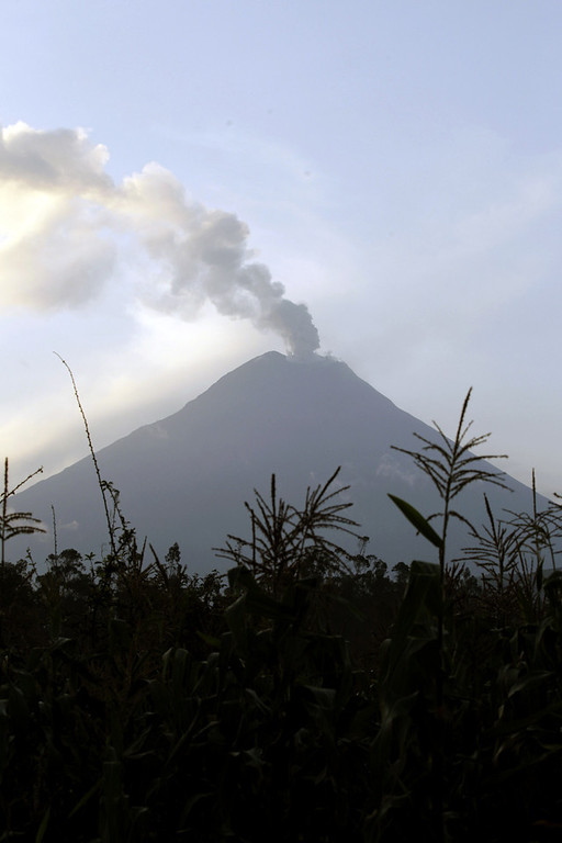 Description of . An ash-filled plume rises from the Tungurahua volcano as seen from Huambalo, Ecuador, Monday, Dec. 17, 2012.  The country's National Geophysics Institute says that a constant plume of gas and ash is rising about half a mile (1 kilometer) above the crater, with ash falling on nearby communities.  (AP Photo/Dolores Ochoa)