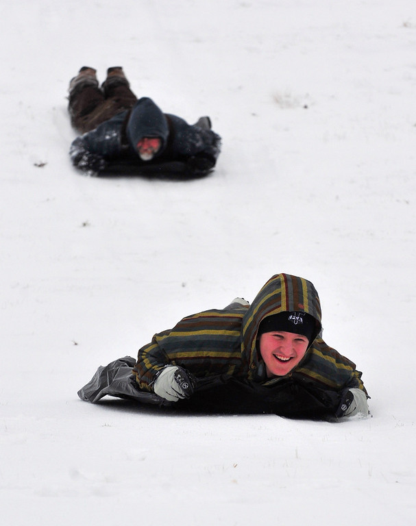 Description of . Aaron Mann, followed by father Kerry slide down a hillside during a winter storm in Gainesville, Ga., Wednesday morning, Feb. 12, 2014. (AP Photo/The Times, Scott Rogers)