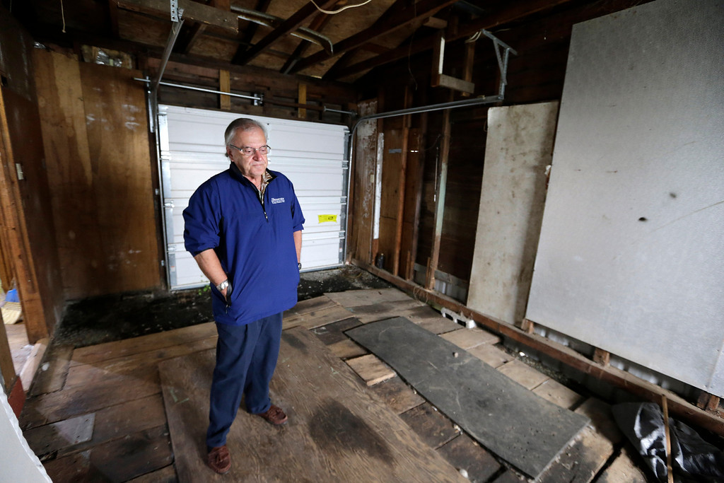 Description of . In this photo taken Monday, Sept. 23, 2013, Dann Sears, curator of the Aberdeen Museum of HIstory, stands in the tiny garage of the childhood home of Kurt Cobain, the late frontman of Nirvana, in Aberdeen, Wash. (AP Photo/Elaine Thompson)