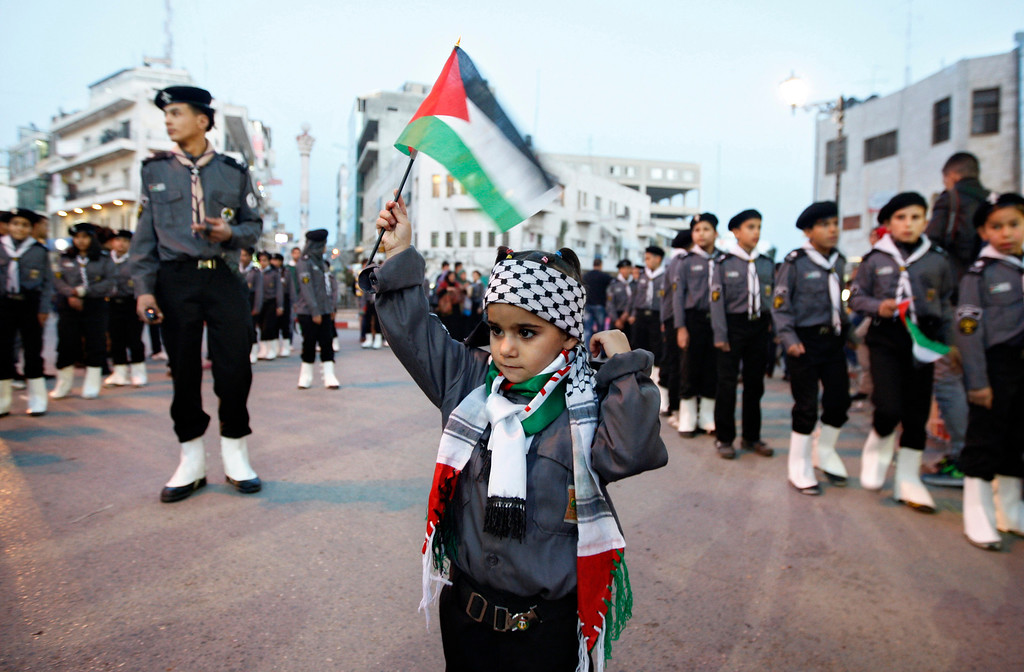 Description of . A Palestinian girl waves a flag during a rally supporting the Palestinian U.N. bid for observer state status, in the West bank city of Ramallah, Thursday, Nov. 29, 2012. The Palestinians are certain to win U.N. recognition as a state on Thursday but success could exact a high price: delaying an independent state of Palestine because of Israel's vehement opposition. (AP Photo/Majdi Mohammed)