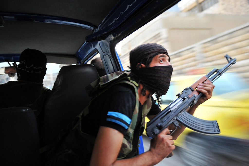 Description of . Syrian rebels hunt for snipers after attacking the municipality building in the city center of Selehattin, near Aleppo, on July 23, 2012, during fights between rebels and Syrian troops. Syrian rebels