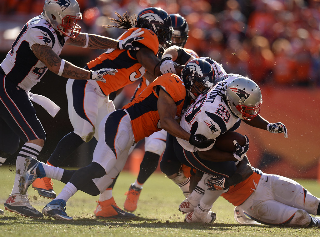 Description of . New England Patriots running back LeGarrette Blount (29) is brought down in the second quarter. The Denver Broncos take on the New England Patriots in the AFC Championship game at Sports Authority Field at Mile High in Denver on January 19, 2014. (Photo by Hyoung Chang/The Denver Post)