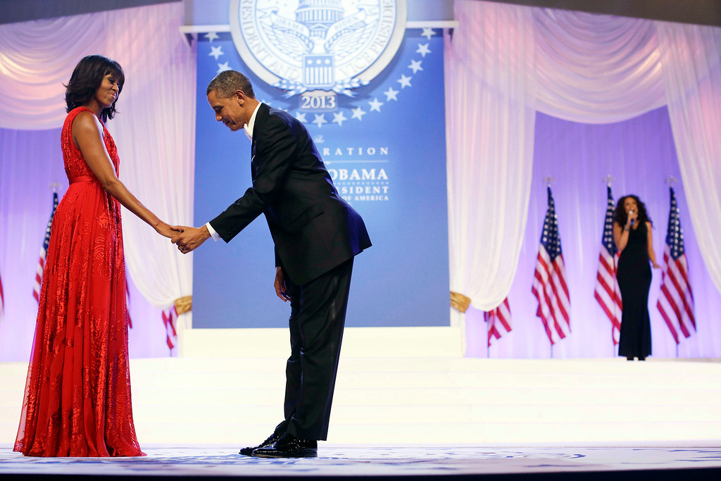 Description of . President Barack Obama bows as he and first lady Michelle Obama, wearing a ruby colored chiffon and velvet Jason Wu gown, gets ready to dance as singer Jennifer Hudson, right, sings Al Green's