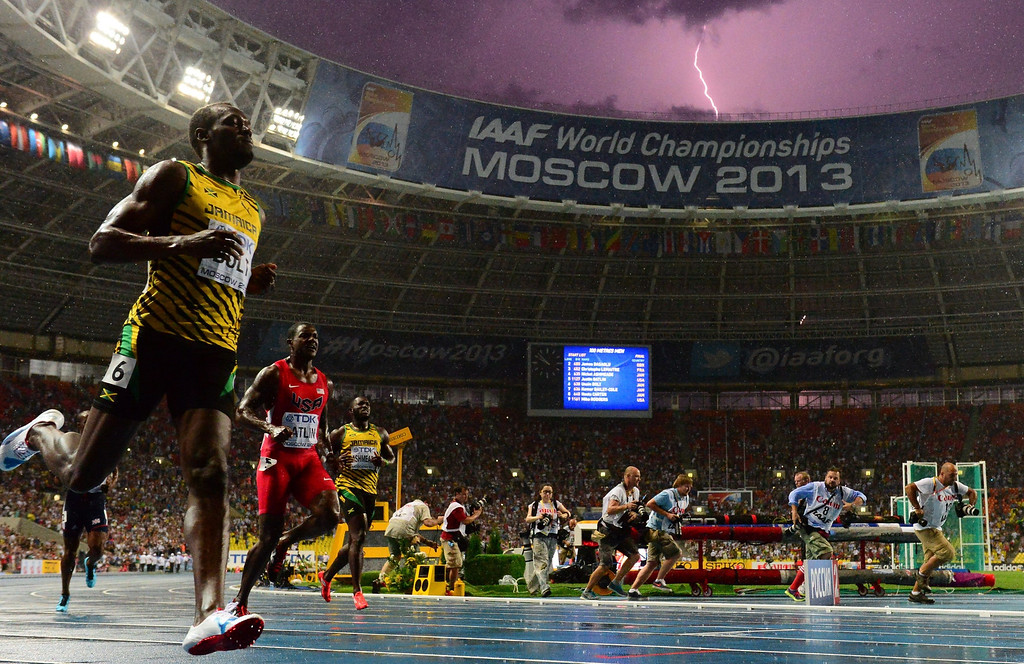 Description of . Jamaica's Usain Bolt (L) wins the100 metre final at the 2013 IAAF World Championships at the Luzhniki stadium in Moscow on August 11, 2013 while a lightning strikes in the sky. Bolt timed a season's best 9.77 seconds, with American Justin Gatlin claiming silver in 9.85sec and Nesta Carter, also of Jamaica, taking bronze in 9.95sec.   OLIVIER MORIN/AFP/Getty Images
