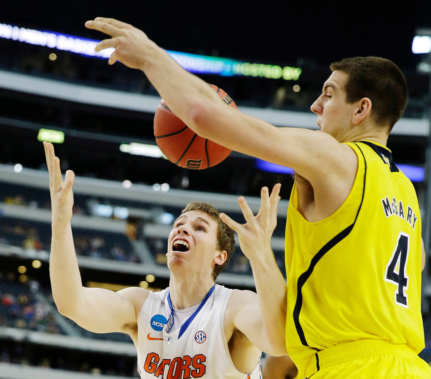 Description of . Michigan\'s Mitch McGary (4) knocks the ball away from Florida\'s Erik Murphy (33) during the first half of a regional final game in the NCAA college basketball tournament, Sunday, March 31, 2013, in Arlington, Texas. (AP Photo/David J. Phillip)