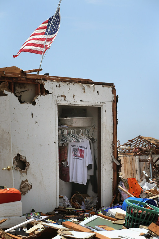Description of . MOORE, OK - MAY 23:  An Oklahoma T-shirt hangs in the closet of a home that was destroyed by a tornado, on May 23, 2013 in Moore, Oklahoma. A two-mile wide EF5 tornado touched down in Moore May 20 killing at least 24 people and leaving behind extensive damage to homes and businesses. U.S. President Barack Obama promised federal aid to supplement state and local recovery efforts.  (Photo by Scott Olson/Getty Images)