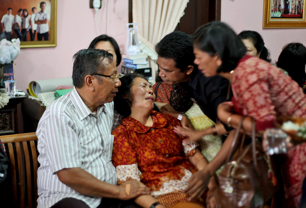 Description of . Family members comfort Chrisman Siregar, left, and his wife Herlina Panjaitan, the parents of Firman Siregar, one of the Indonesian citizens registered on the manifest to have boarded the Malaysia Airlines jetliner flight MH370 that went missing over the South China Sea, at their residence in Medan, North Sumatra, Indonesia, Sunday, March 9, 2014. Military radar indicates that the missing Boeing 777 jet may have turned back, Malaysia's air force chief said Sunday as scores of ships and aircraft from across Asia resumed a hunt for the plane and its 239 passengers. (AP Photo/Binsar Bakkara)