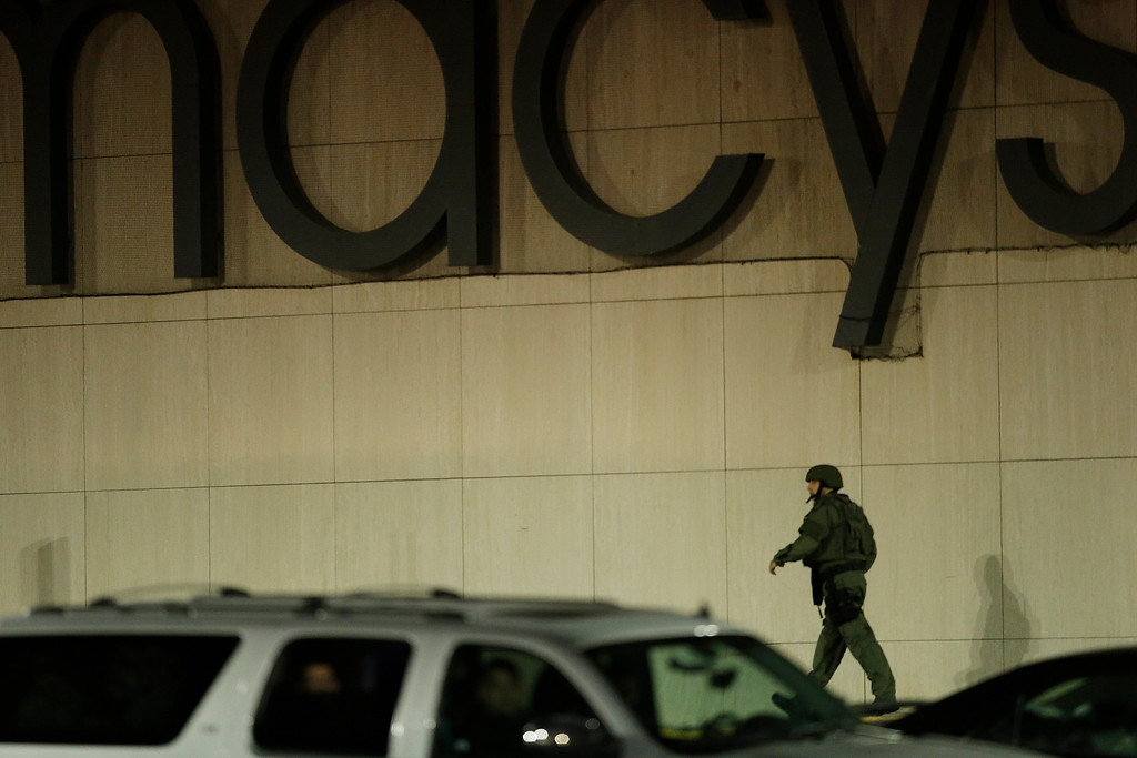 Description of . An official wearing tactical gear walks outside of the Garden State Plaza Mall following reports of a shooter, Monday, Nov. 4, 2013, in Paramus, N.J. Hundreds of law enforcement officers converged on the mall Monday night after witnesses said multiple shots were fired there. (AP Photo/Julio Cortez)