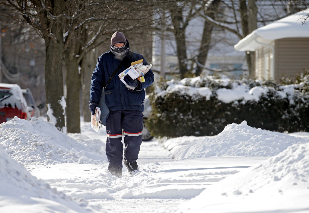 Description of . Letter carrier Steve Zona delivers mail through snow and subzero temperatures in Berea, Ohio Tuesday, Jan. 28, 2014. Another arctic front descended on the midwest overnight closing schools and some businesses. (AP Photo/Mark Duncan)