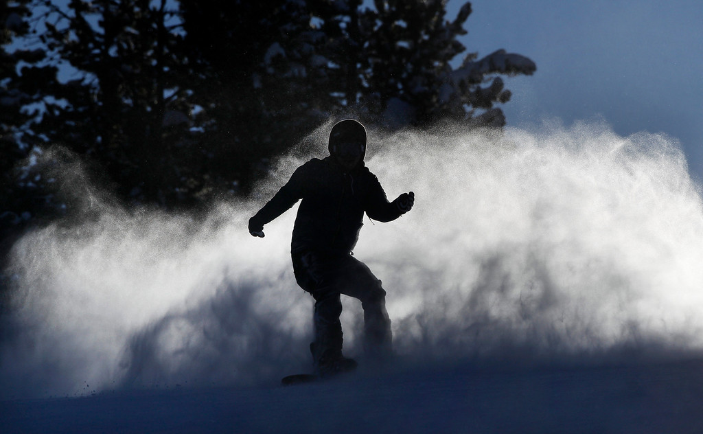 Description of . A snowboarder, silhouetted by the setting sun, kicks up a wake of snowy mist, at Winter Park alpine resort, in Colorado, Thursday Dec. 20, 2012. Fresh snow earlier in the week, with more expected before Christmas, has left much of Colorado ski-country replenished after a relatively warm and dry Fall. (AP Photo/Brennan Linsley)