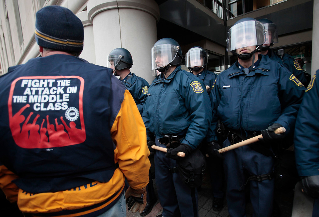 Description of . A United Auto Worker (L) union member faces a line of police wearing riot gear, who are preventing people from entering the state building with the office of Michigan Governor Rick Snyder, in Lansing, Michigan December 11, 2012.  Michigan legislators on Tuesday approved laws that ban mandatory membership in public and private sector unions, dealing a stunning blow to organized labor in the home of the U.S. auto industry. REUTERS/Rebecca Cook