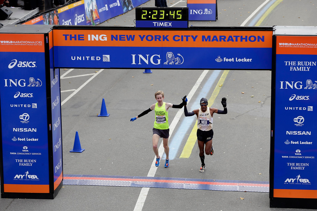 Description of . American runners Michael Cassidy, left, and Meb Keflezighi cross the finish line holding hands  at the 2013 New York City Marathon in New York, Sunday, Nov. 3, 2013.  (AP Photo/Seth Wenig)