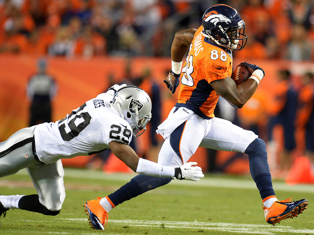 Description of . Denver Broncos wide receiver Demaryius Thomas (88) outruns a tackle in the first quarter. The Denver Broncos took on the Oakland Raiders at Sports Authority Field at Mile High in Denver on September 23, 2013. (Photo by John Leyba/The Denver Post)