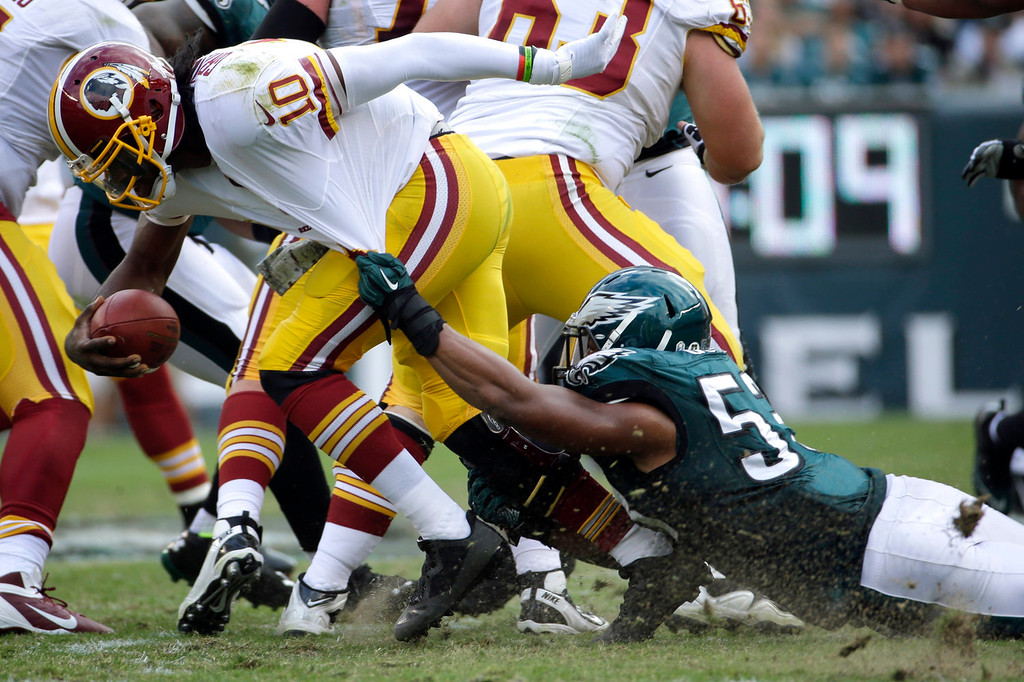 Description of . Washington Redskins quarterback Robert Griffin III (10) is dragged to the turf by Philadelphia Eagles linebacker Najee Goode during the first half of an NFL football game in Philadelphia, Sunday, Nov. 17, 2013. (AP Photo/Matt Slocum)