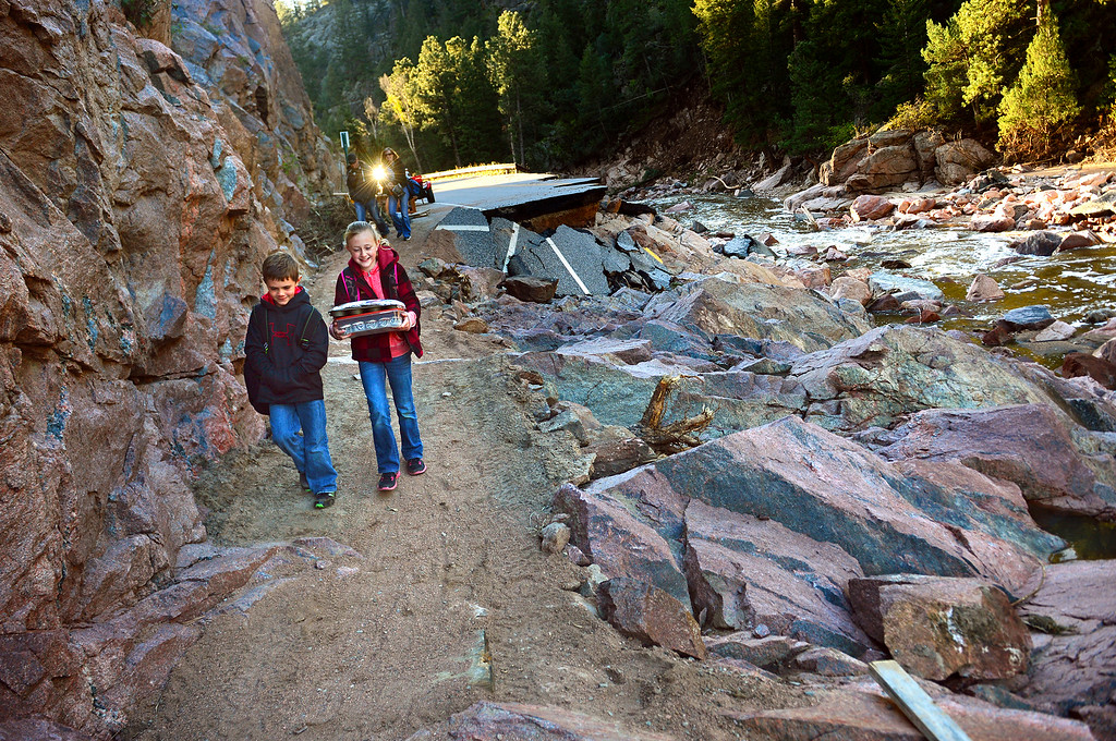 Description of . Kody Payne, 7, and his sister Kaelyn, 10, walk along a dirt path next to what used to be U.S. 36 near Pinewood Springs, Colo. on Sept. 24, 2013. The siblings were heading back to Estes Park Elementary School for the first time since floods damaged the town. Kaelyn carries trays of cupcakes to celebrate her 10th birthday, while their parents, Judd and Sherami, walk behind them. The community of Pinewood Springs was left an island after the massive flood took out all major roads and bridges. Residents, who refused to evacuate, worked aggressively to make this path for access to Estes Park. They park their cars at Elk Meadows, above the damaged highway, then make the trek back and forth to cars on the other side to get home. The walk is about a mile.