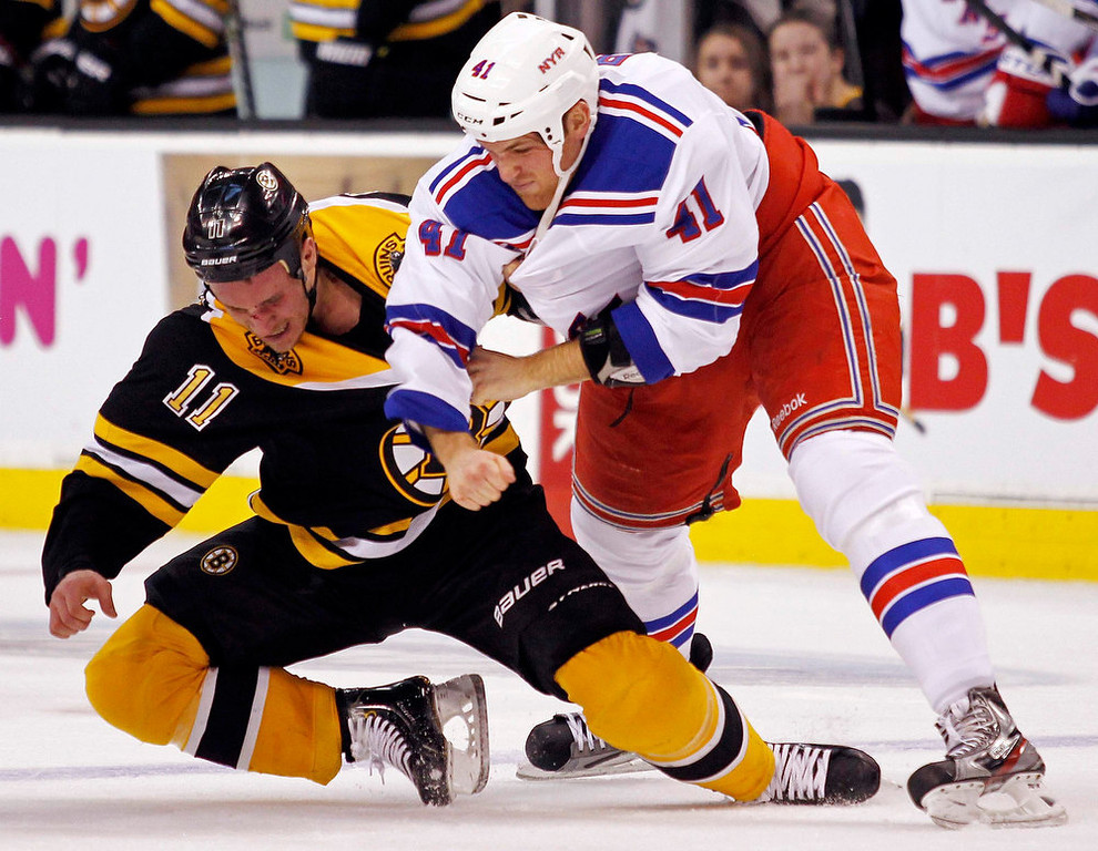 . Boston Bruins\' Gregory Campbell (L) is pushed to the ground as he fights with New York Rangers\' Stu Bickel during the second period of their NHL hockey game at TD Garden in Boston, Massachusetts January 19, 2013. REUTERS/Jessica Rinaldi