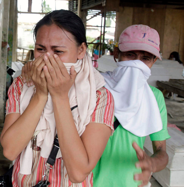Description of . Residents cry while looking for their missing relatives amongst the coffins of typhoon Bopha victims lying at a destroyed market turned into a mortuary, in New Bataan town in Compostela Valley, southern Philippines December 8, 2012. Philippine President Benigno Aquino declared a state of national calamity on Saturday, four days after this year\'s strongest typhoon left nearly 1,000 people dead or missing mostly in the country\'s resource-rich south. REUTERS/Erik De Castro