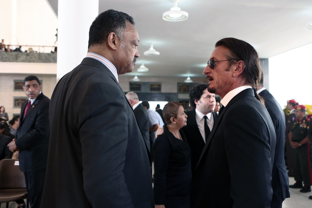 Description of . Handout picture released by the Venezuelan presidency showing US Reverend Jesse Jackson (L) talking with US Actor and filmmaker Sean Penn during the funeral of Venezuelan President Hugo Chavez, in Caracas, on March 8, 2013.    AFP PHOTO/PRESIDENCIA/HO
